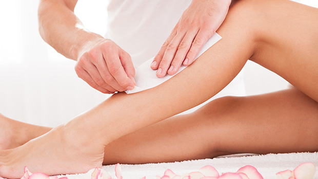 Beautician waxing a womans leg applying a strip of material over the hot wax to remove the hairs when pulled